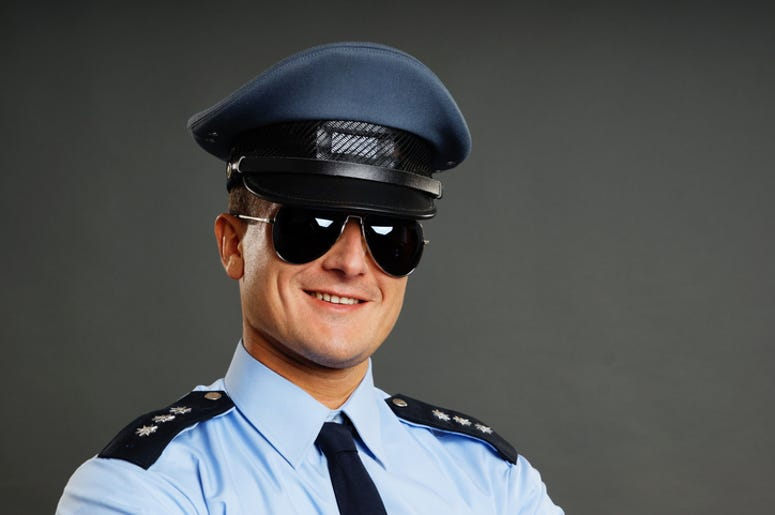 Portrait of smiling policeman in sunglasses on the gray background