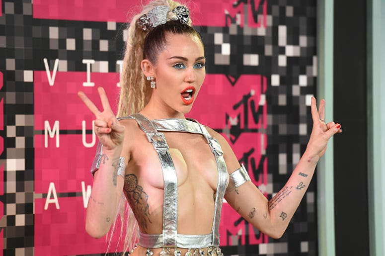 Host Miley Cyrus, styled by Simone Harouche, wearing a custom Versace outfit and boots, attends the 2015 MTV Video Music Awards at Microsoft Theater on August 30, 2015 in Los Angeles, California.