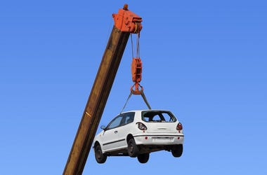 White car hanging by the arm of a crane