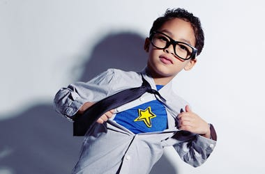 Adorable mixed race boy ripping off his dress shirt to uncover his superhero costume underneath.