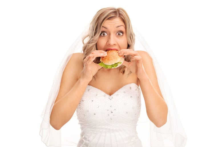Surprised blond bride eating a sandwich and looking at the camera isolated on white background