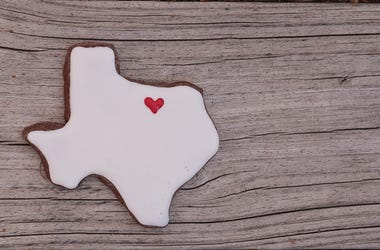 Texas shaped sugar cookie with white icing and a red heart on a rustic wood table.