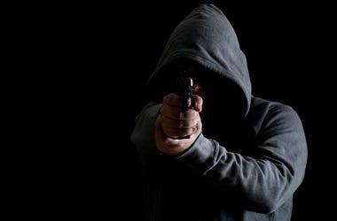 Man in green hoodie points gun