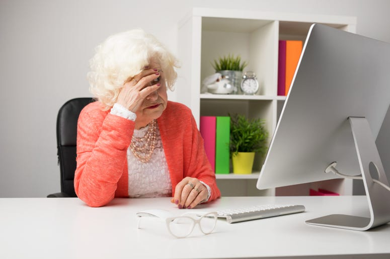Older woman working at the office and having headache