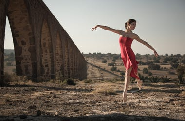 Ballerina wearing with a red dress and dancing in a colonial landscape.