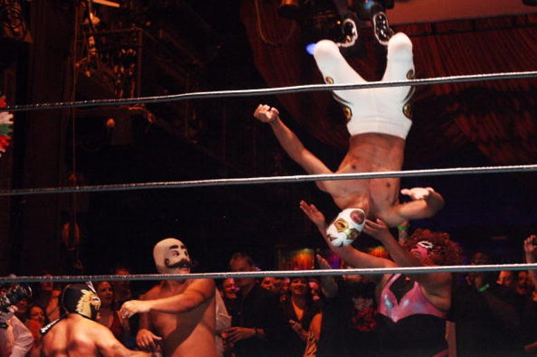 Luchadores, traditional Mexican wrestlers, fly over the ropes and into the audience as they perform at the Lucha Vavoom Cinco de Mayan! show at the Mayan Theater on Cinco de Mayo, May 5, 2009 in Los Angeles, California. Lucha Vavoom combines elements of t