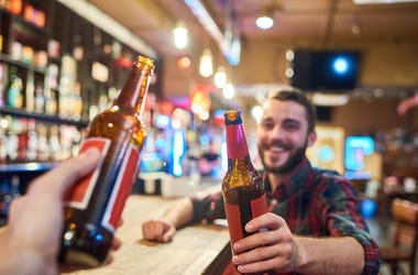 Portrait of happy bearded man clinking beer bottles with friends while having fun in pub sitting at bar counter, focus on foreground