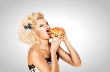 Beautiful pinup model eating a hamburger on grey background.