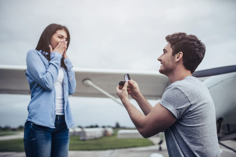 Beautiful romantic couple is standing near private plane in airport. Handsome man is making proposal to his attractive young woman.