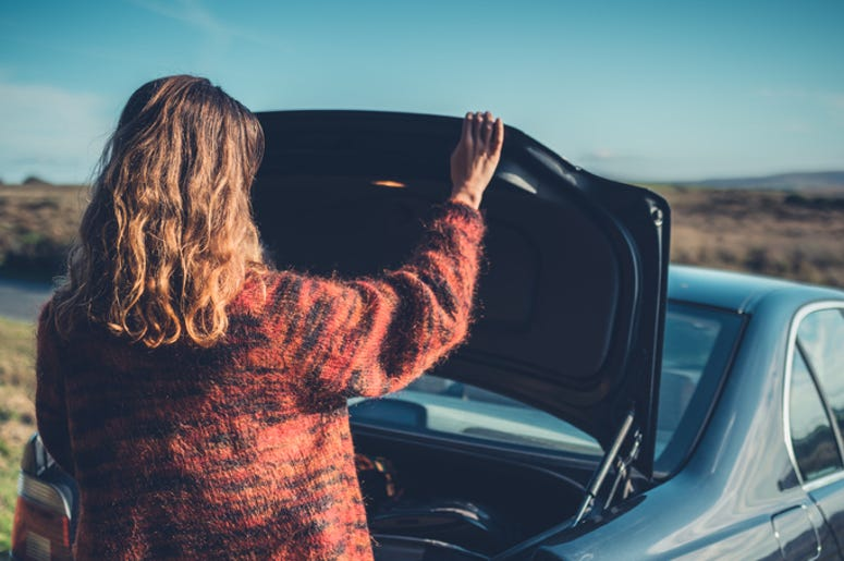 A young woman is opening the trunk of her car in the wilderness