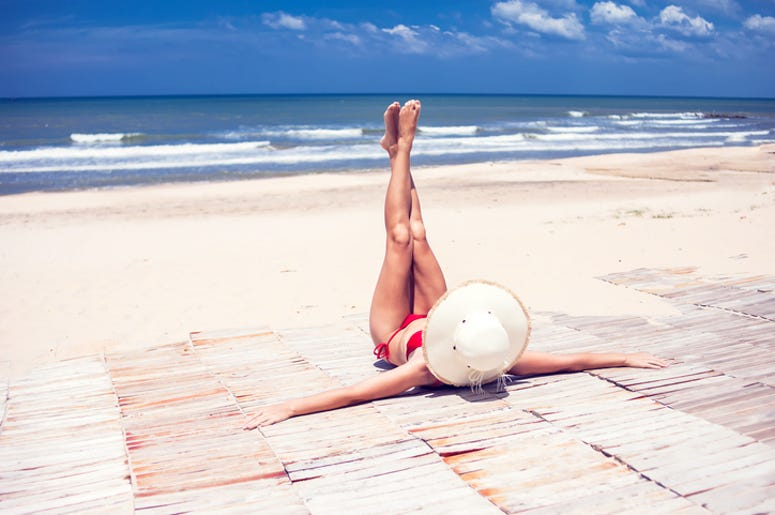 Young woman in straw hat lying on a tropical beach, stretching up slender legs. Blue sea in the background. Summer vacation concept.