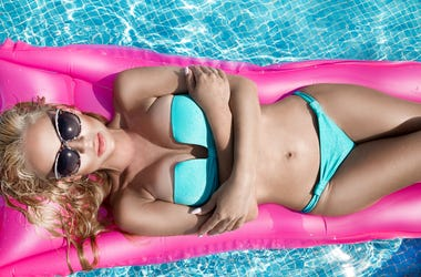 Beautiful model model with long blonde wet hairs, sunglasses and bikini swims in the pool on a pink mattress ,. Curly, beach.