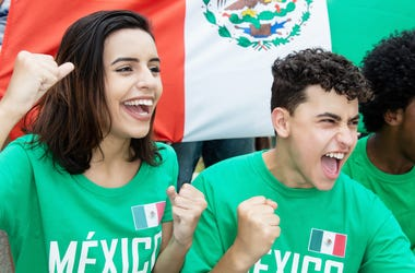Young soccer fans from Mexico with mexican flag outdoors at stadium