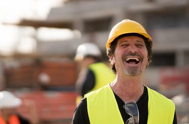 Front view portrait of a caucasian civil engineer wearing yellow reflective jacket and hardhat laughing looking at the camera