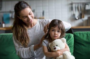 Caring loving mother brushing kid daughters hair sitting on sofa.