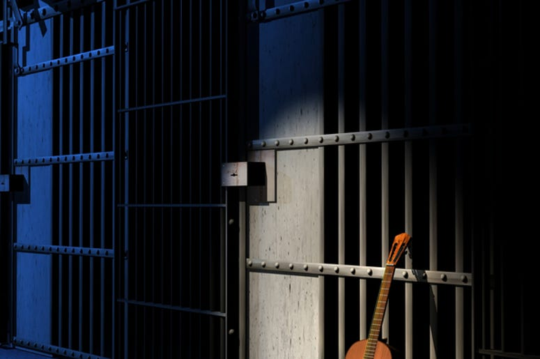 Classic guitar in prison. Blue light for abstract reference to the blues music
