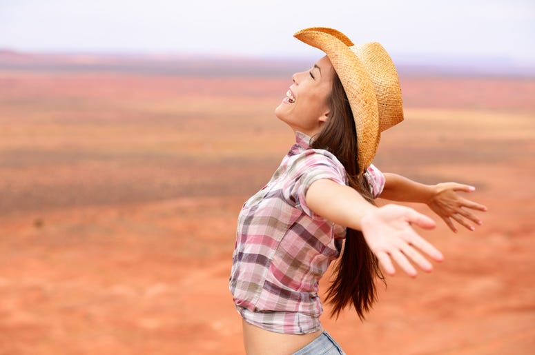 Cowgirl - woman happy and free on american prairie.