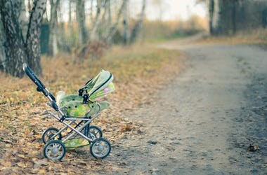 Empty baby stroller left in a park on a autumn day