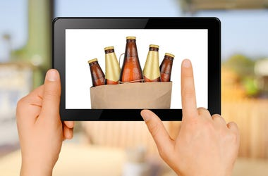 Hands holding tablet PC and ordering beer via internet