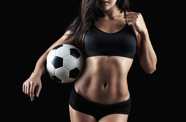 Beautiful body of fitness model holding soccer ball. Athlete, bodybuilding.