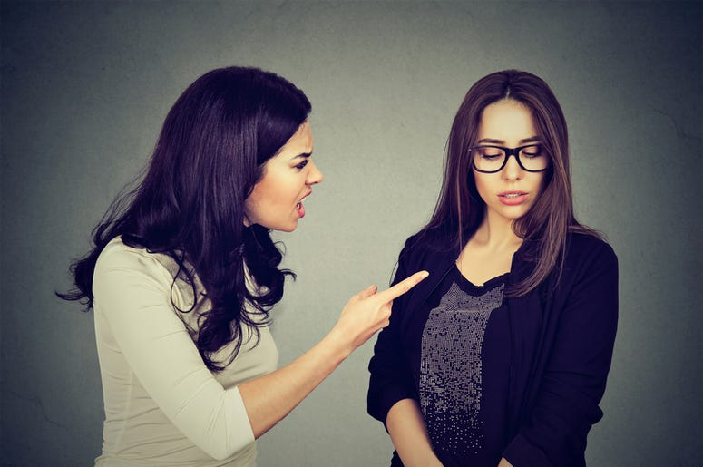 Angry woman scolding her scared shy sister or friend.