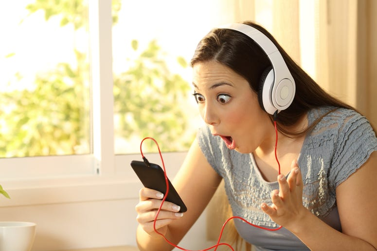 Amazed woman listening music finding offers on line in a smart phone in her room