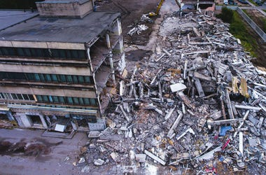A process of buliding demolition, demolished house, shot from air with drone. Earthquake, crusher.