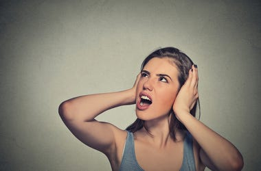 Closeup portrait young unhappy stressed woman covering her ears looking up stop making loud noise it's giving me headache isolated on gray wall background. Negative emotion face expression feeling