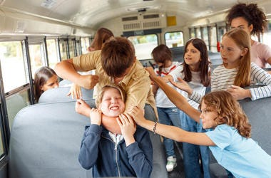 Group of children classmates going to school by bus boy strangling kid punching angry while others trying to stop him from violence