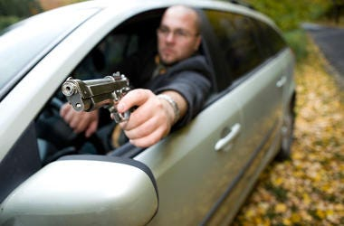 angry man with gun driving car