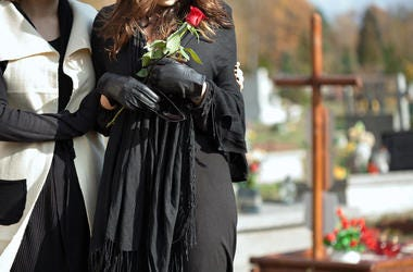 Mother holding her daughter standing above grave of family member