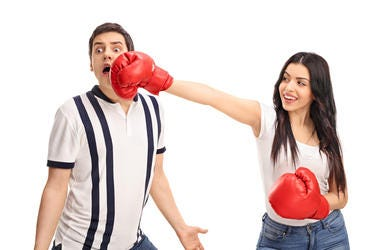 Cheerful woman punching her boyfriend with boxing gloves isolated on white background