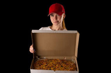 young attractive girl with a pizza box isolated on black background