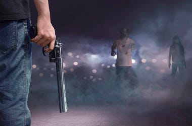 Brave man with jeans pants holding gun looking at zombies walking into him