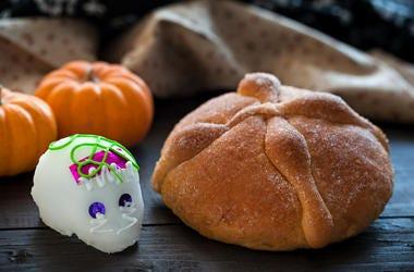 Dia De Los Muertos (Day of the Dead) Sugar Skull ( Calaverita) and bread of Dead Offering, on wooden table, selective focus