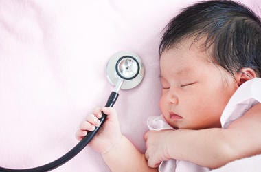 Cute asian newborn baby girl sleeping and holding medical stethoscope in hand