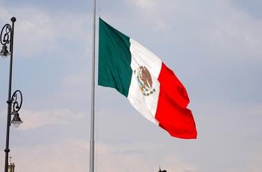 Waving mexican flag at the center of the country in the mexico city main plaza, green white and red flag hanging in a metallic post, waving with the wind