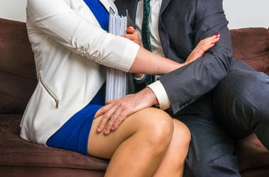 Man touching woman`s knee - sexual harassment in office. Professional, embarrassed.