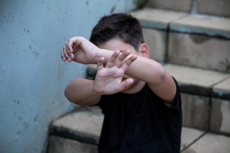 A little boy protects himself with his palms and covers his face. Stop abusing boy violence. violence, terrified , A fearful child