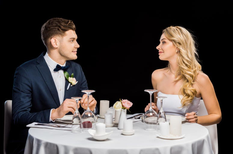 handsome groom and beautiful bride sitting at served table isolated on black - stock photo