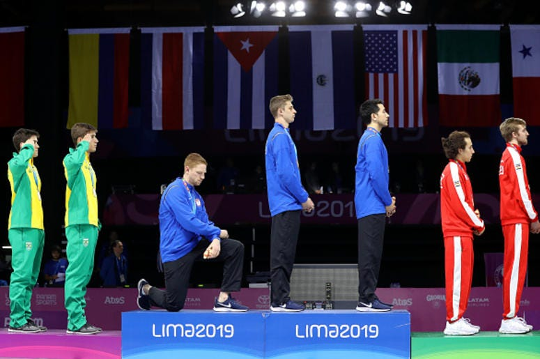 Gold medalist Race Imboden of United States takes a knee during the National Anthem Ceremony in the podium of Fencing Men's Foil Team Gold Medal Match Match on Day 14 of Lima 2019 Pan American Games at Fencing Pavilion of Lima Convention Center on August