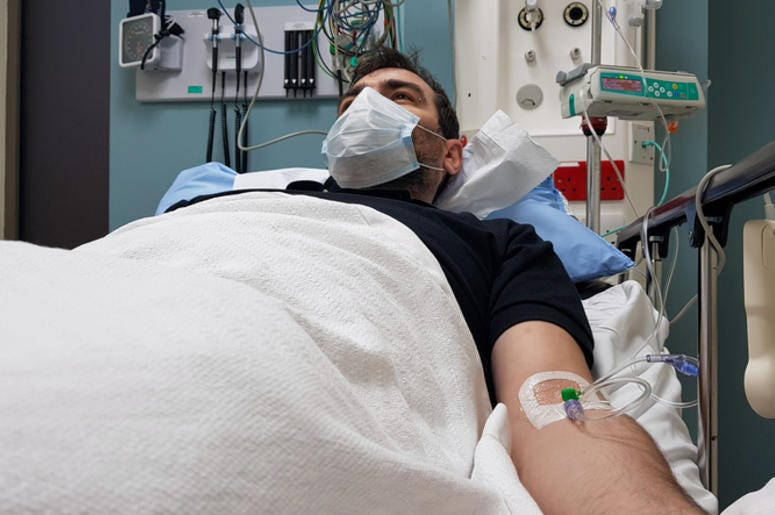 Young man lying in hospital bed. Recovering in modern hospital wards, covered with blanket, face mask and with intravenous needle in his arm