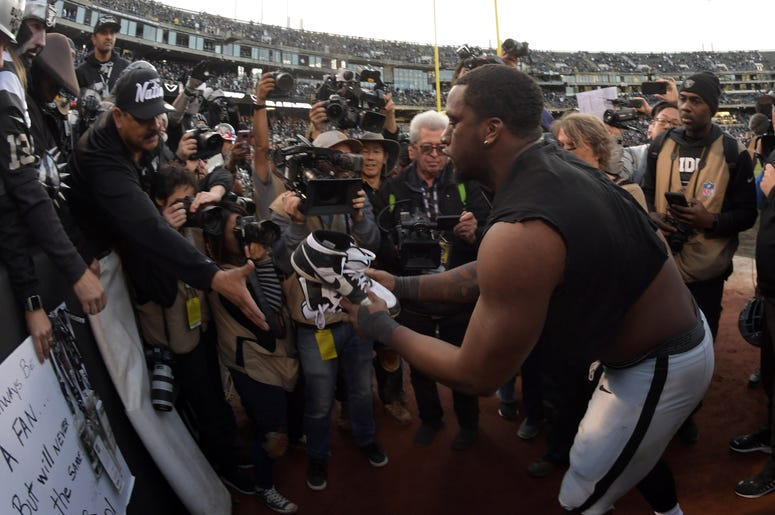 Oakland Raiders defensive end Clelin Ferrell (96) gives his cleats to a fan after the Raiders final game against the Jacksonville Jaguars at the Oakland-Alameda Coliseum before relocating to Las Vegas...