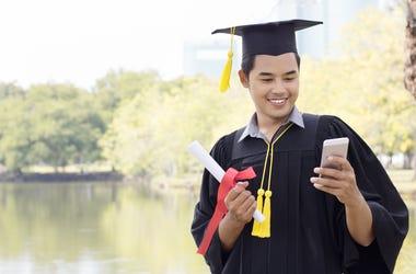 graduate holding phone