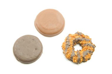 Three Delicious Cookies that include a chocolate peanut butter, coconut ring, and a thin chocolate mint cookie that are sold door to door.