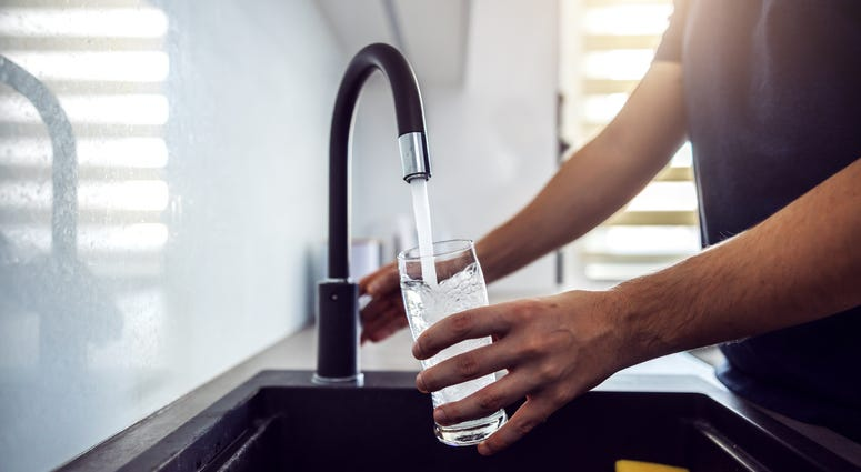 Close up of man pouring water from kitchen sink