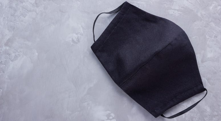 A black face mask on a gray background