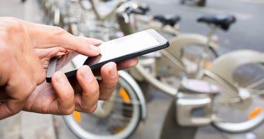 Man renting bike through a smart phone app