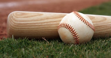 Close-up of baseball and bat resting on the field