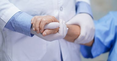 Doctor holding hands of senior elderly woman patient